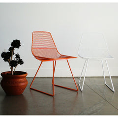 Orange and White Bend Ethel Chairs in Room with Plant