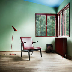 Ole Wanscher Beak Chair in red leather with black oak frame  in room with red Louis Poulsen floor lamp.