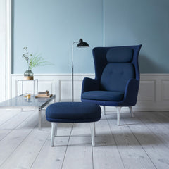Fritz Hansen Dark Blue Ro Chair and Ottoman in room with Poul Kjaerholm Coffee Tablea and Kasier Idell Floor Lamp