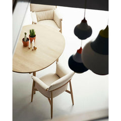 Eoos Embrace Dining Chairs by Carl Hansen and Son in room with Louis Poulsen Pendant Lights