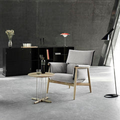 Carl Hansen EOOS lounge table E021 in room with Embrace Lounge chair and Louis Poulsen lamps
