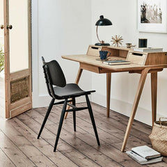 ercol Treviso desk in Oak by Matthew Hilton in room with Black Butterfly Chair