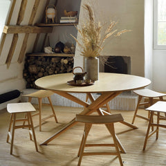 Ethnicraft Oak Mikado Dining Table Round in room with Osso Stools