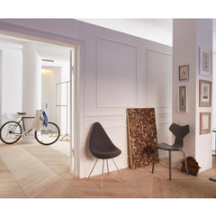 Fritz Hansen Arne Jacobsen Drop Chair in room with Grand Prix Chair and Bicycle