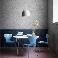 Fritz Hansen Gam Fratesi Suspence Pendant in room with Super Elliptical Table and light blue Series 7 Chairs