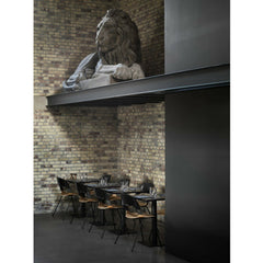 Fritz Hansen PAIR chairs by Benjamin Hubert Black and Oak in Elegant Restaurant with Lion Statue Angled View