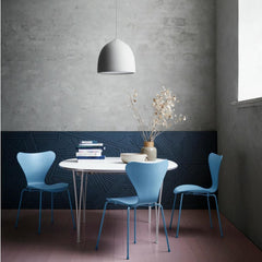 Fritz Hansen Super Elliptical Table in room with Trieste Blue Series 7 Chairs and Suspense Pendant Light