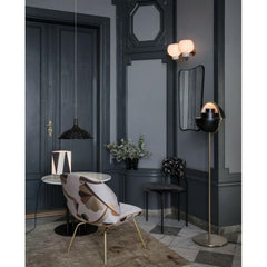 GUBI Muli Lite Floor Lamp Black and Brass in room with Beetle Lounge Chair and Coco Dining Chair