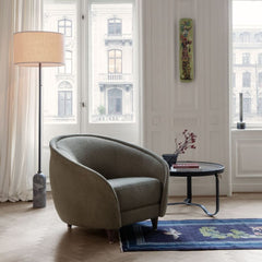 GUBI Revers Lounge Chair in room with Gravity Floor Lamp and Adnet Coffee Table
