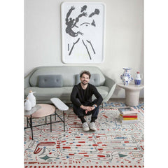 Jaime Hayon in his living room with Hayon x Nani Rug, Favn sofa, and palette coffee table