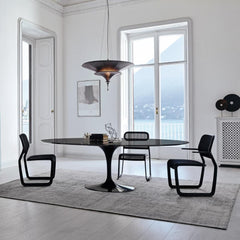 Knoll Saarinen Oval Dining Table Black in room with Mark Newson Chairs