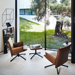 Knoll Leather Pilot Swivel Lounge Chairs by Barber Osgerby in room with floor to ceiling windows
