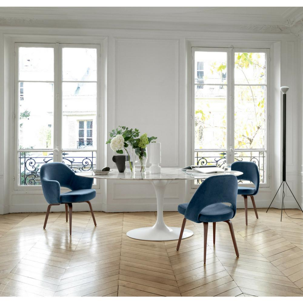 Knoll saarinen oval dining table in room with blue velvet saarinen executive chairs with wood legs