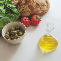 Marquina Oil Cruet in Kitchen with Olives and Vegetables and Artisanal Bread