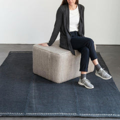 Nani Marquina Mia Rug Pouf in Stone with Mia Rug Blue in Room