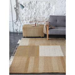 Nani Marquina Tres Rug Ochre in room with Pouf