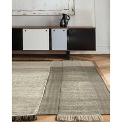 Nani Marquina Tres Rug Black in room with sideboard