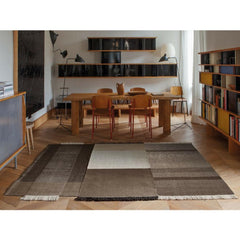 Nani Marquina Tres Rug Chocolate in room with Prouve Standard Chairs and Serge Mouille Lamps