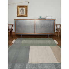Nani Marquina Tres Rug Sage in room with zinc sideboard