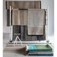 Nani Marquina Tres Rugs layered on racks