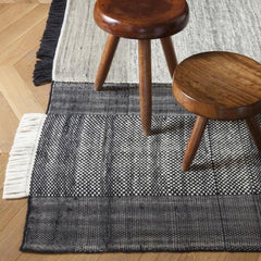 Nanimarquina Tres Rug Black in room with stools