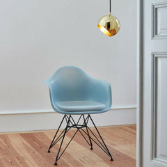 Nyta Tilt Globe Pendant Brass in room with Eames Eiffel Chair