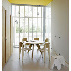 Prouve Gueridon Table in room with Standard Chairs Yellow Ceiling Vitra