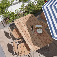Skagerak Lilium Teak Dining Table and Chairs outdoors with umbrella