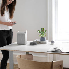 Vifa Oslo Speaker Pebble Grey in home office with woman