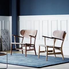 Wegner CH22 Lounge Chairs in Room with Woodlines Rug by Carl Hansen and Son