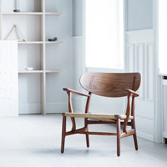 Wegner CH22 Lounge Chair in Walnut in Room by Carl Hansen and Son