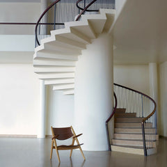 Wegner Walnut and Oak CH28 Lounge Chair in Room with Spiral Staircase Carl Hansen and Son