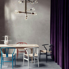 Wegner Colored Wishbone Chairs in room with Wegner dining table and modern chandelier