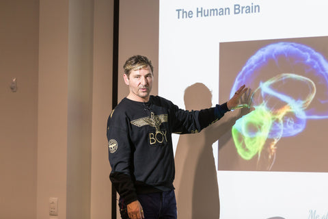 Nathan Wallis presenting on stage brain