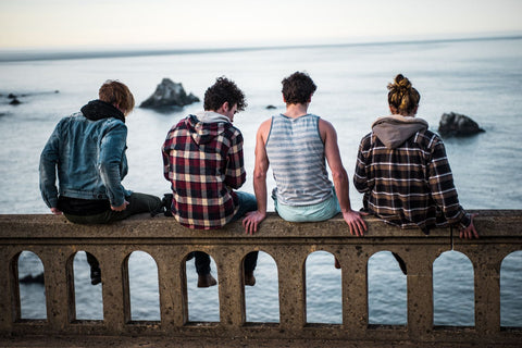 Teenagers sitting on a fence by the ocean