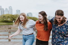 three teenage girls walking with linked arms