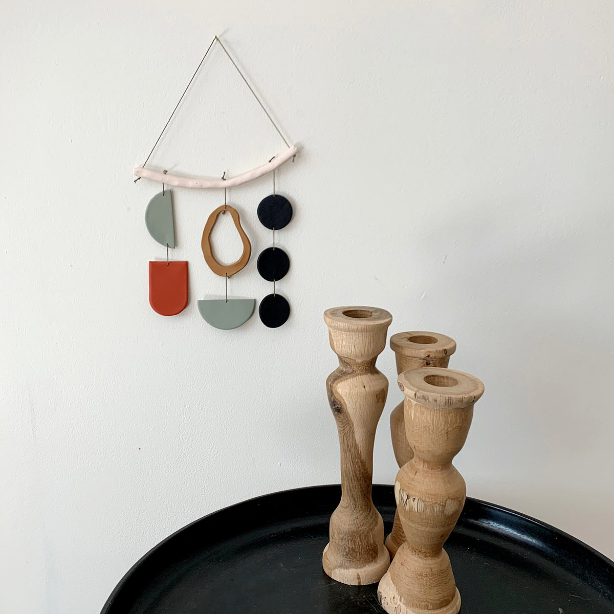 a clay wall decoration with a cream bar across the top and multicolored pieces hanging down from it in tones of sage green, terra cotta, camel, & black