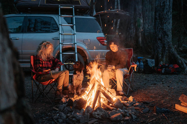 A couple is sitting around a fire with their dog at their campsite. Their SUV is behind them with their SMRT Tent roof top tent open.