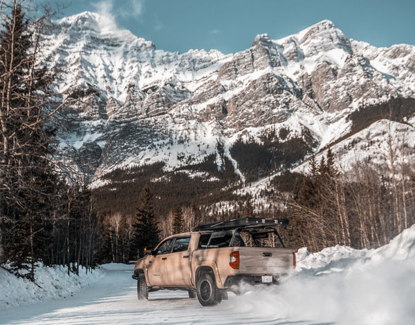Toyota Tacoma driving on a backroad in the snow, with a mountain view in the background