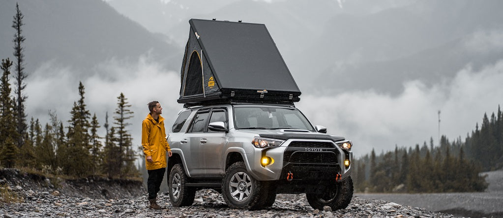 A guy with a rain jacket on looking at a Toyota 4Runner with a SMRT Summit Suit roof top tent on it. The tent is closed and it's raining out.