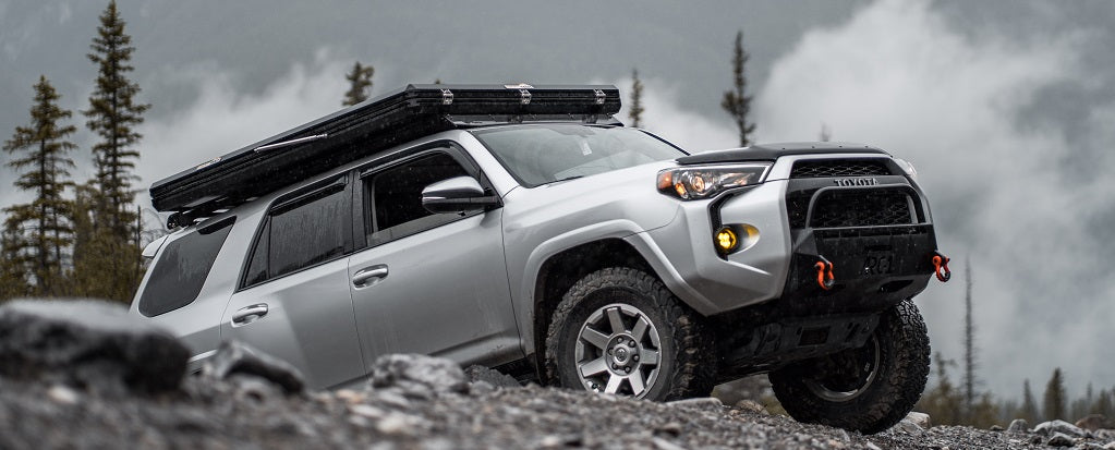 A Toyota 4Runner with a SMRT Summit Suit roof top tent on top driving over some difficult rocky terrain.