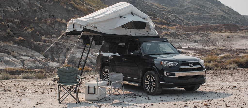 A SMRT soft shell roof top tent set up with chairs and a cooler outside. On top of a highlander in the desert of Drumheller Alberta.