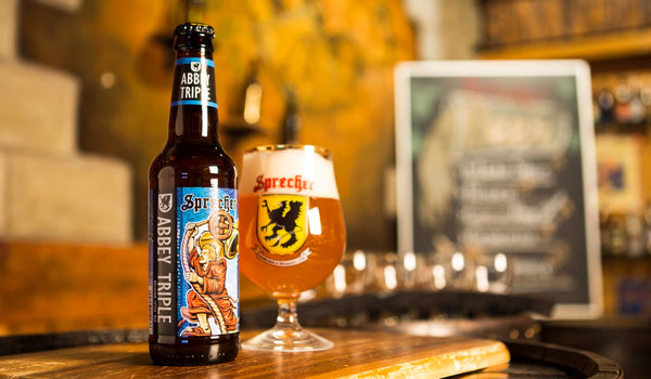A 12oz bottle of Sprecher Abbey Triple next to a snifter glass of Sprecher Abbey Triple.