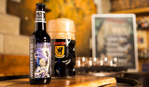 A 12oz bottle of Sprecher Black Bavarian with a 1 liter dimple mug of Sprecher Black Bavarian in the background.