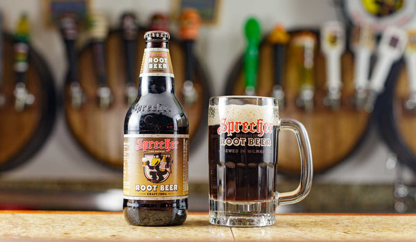 A 16 oz bottle of Sprecher Root Beer next to a mug of Sprecher root beer.