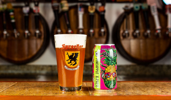A pint glass of Sprecher Pineapple X-Press next to a can of Sprecher Pineapple X-Press.