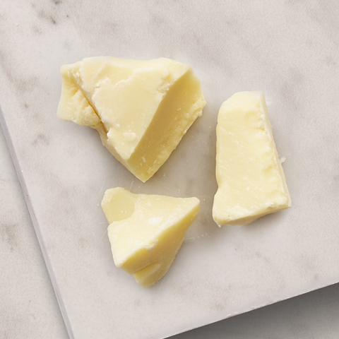 Pieces of cocoa butter on a marble surface