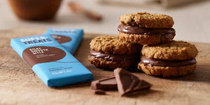 Bars of carob chocolate next to three delicious cookie sandwiches