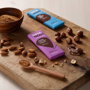 Supertreats carob chocolate bars on a chopping board with a bowl of coconut sugar, carob pieces, almonds and hazelnuts