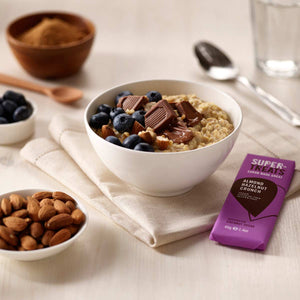 Supertreats carob chocolate next to a healthy porridge bowl topped with carob pieces and blueberries